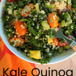 Taking a forkful of edamame Kale Quinoa Salad in a white bowl with tomatoes, quinoa, mangos and pepitas