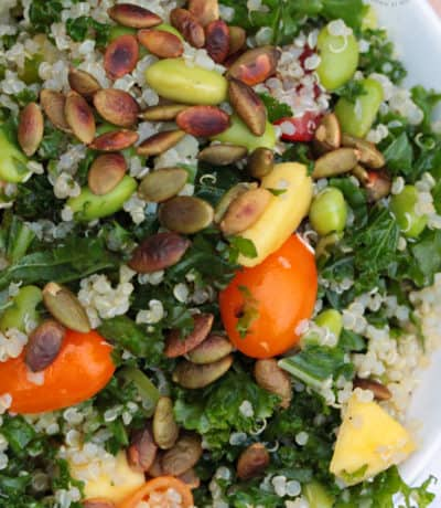 closeup of Kale Quinoa Salad in a white bowl with tomatoes, quinoa, mangos and pumpkin seeds in a white bowl