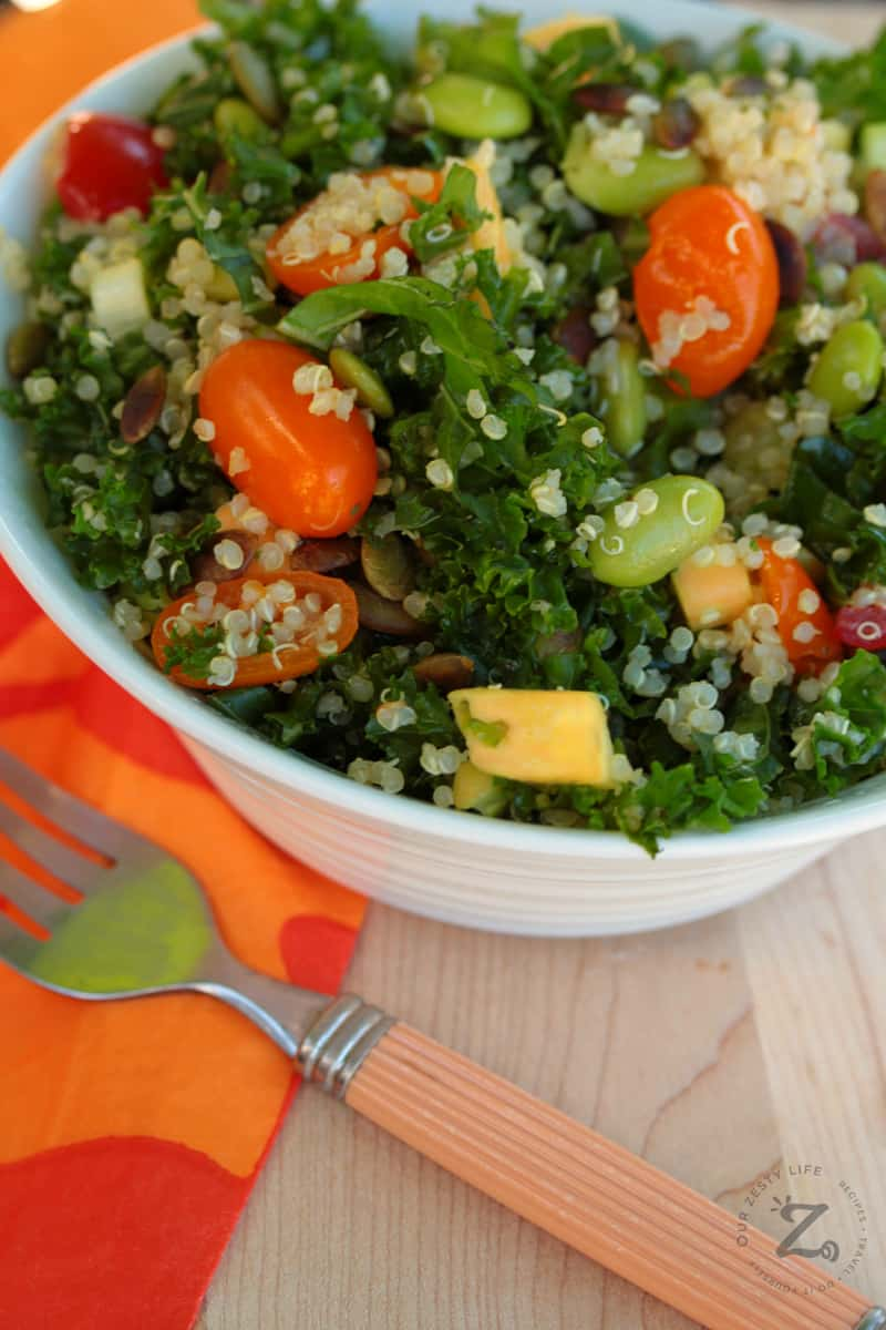 Kale Quinoa Salad in a white bowl with tomatoes, quinoa, mangos and pepitas with a fork and orange napkin on the side