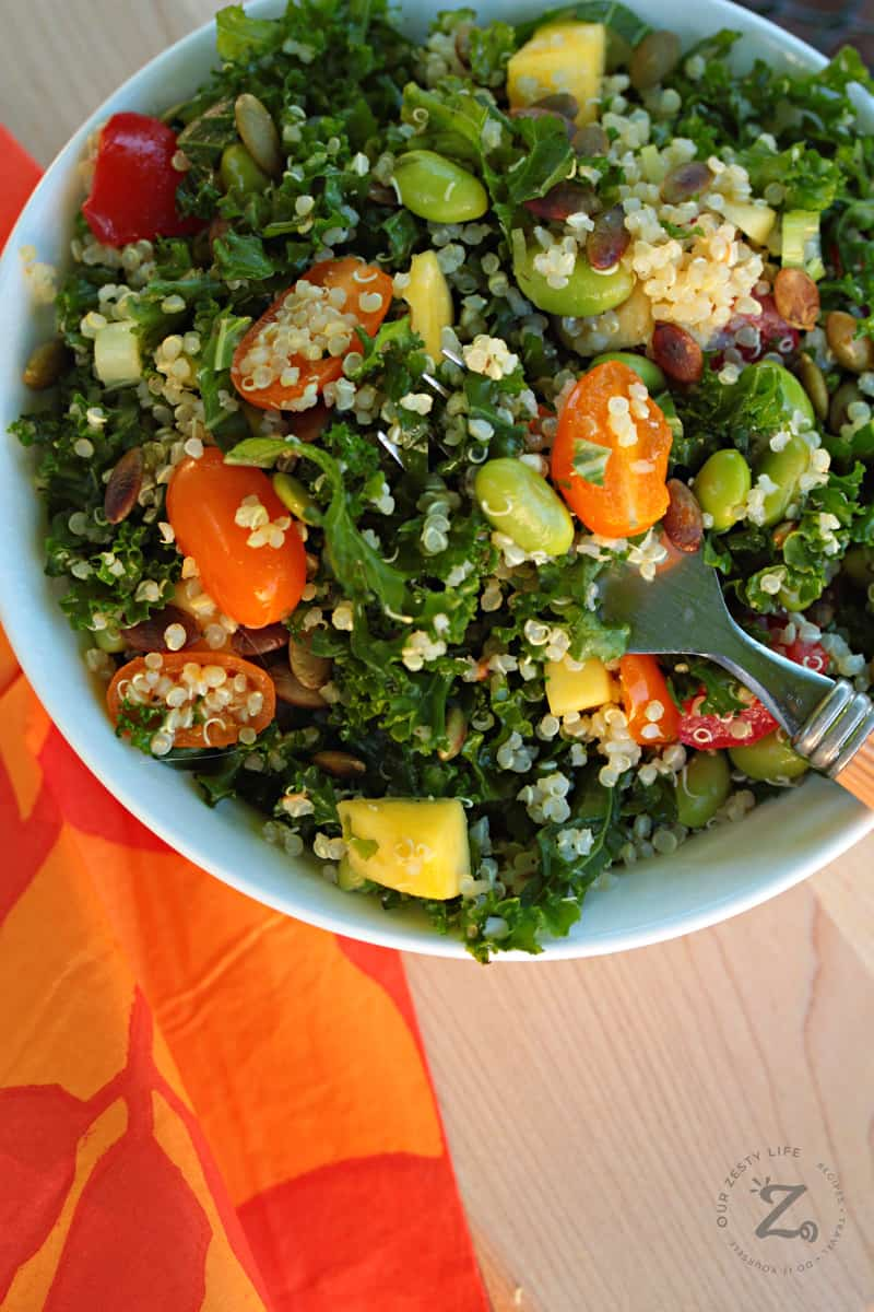 a forkful of Kale Quinoa Salad in a white bowl with tomatoes, quinoa, mangos and pepitas with an orange napkin on the side