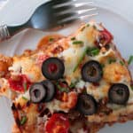 Mexican lasagna piece with olives on a white plate with a fork