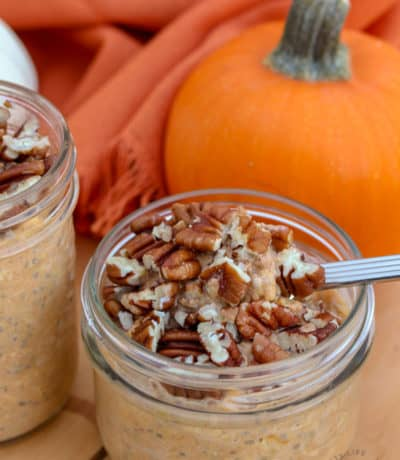 mason jars with pumpkin overnight oats topped with pecans, taking a spoonful from one, with a pumpkin in the background