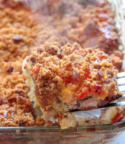 cut piece of breakfast bake on a spatula with the breakfast casserole in the baking pan in the background