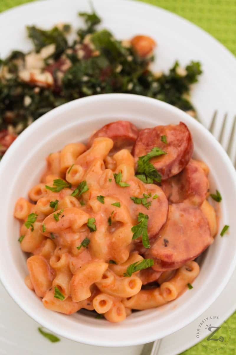 overhead of Instant Pot Pasta with sausage and parsley garnish in a white bowl with a kale salad and fork on the side