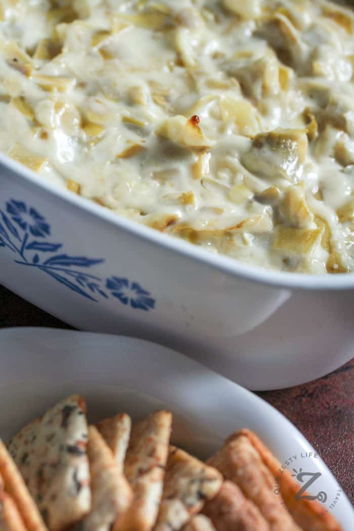 the best artichoke dip in a white corning ware casserole dish with a dish of crackers on the side