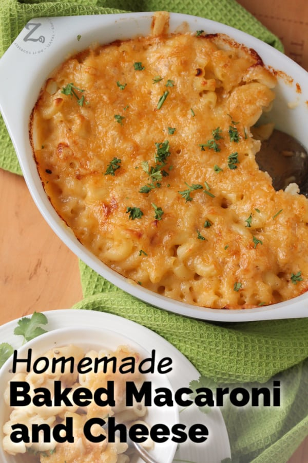 overhead of baked macaroni and cheese recipe in a white casserole dish garnished with parsley and a white bowl with a serving of baked macaroni and cheese
