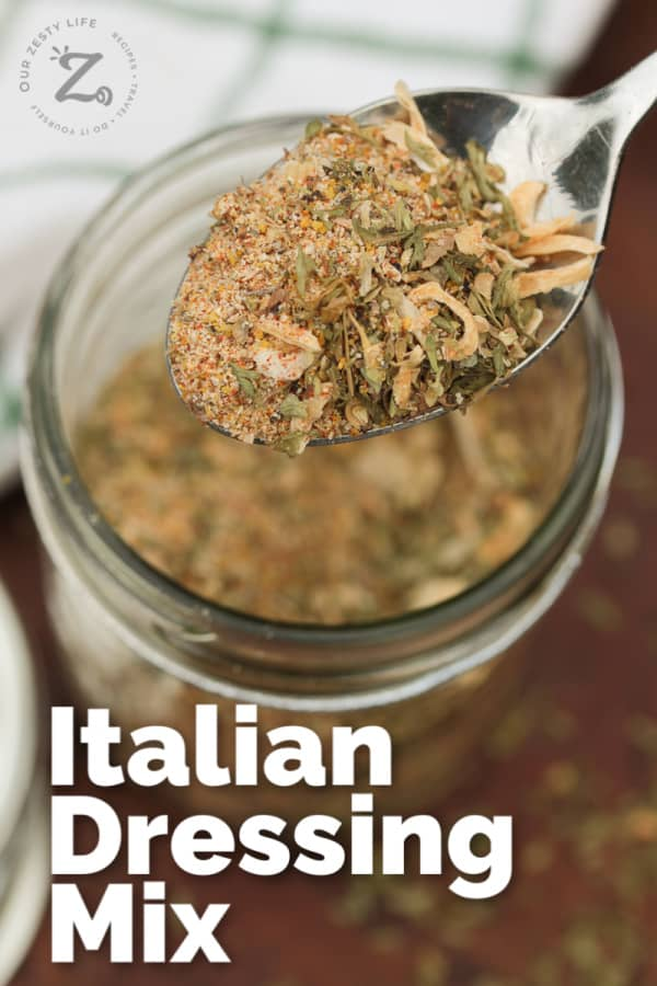 closeup of dry Italian dressing mix on a spoon with a glass jar filled with mix in the background