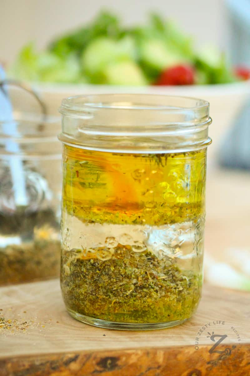 homemade Italian dressing layered in a mason jar not mixed with a salad in the background