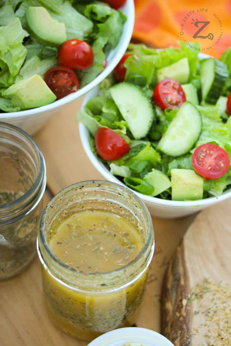 Italian salad dressing in a mason jar with bowls of salad, and Italian dressing mix in the background