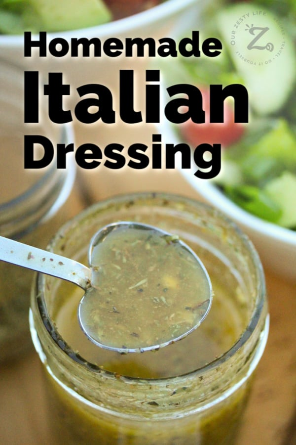 a spoonful of homemade Italian dressing with a mason jar filled with dressing and a salad in the background