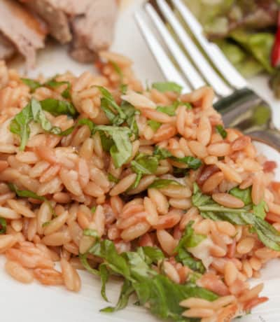 Parmesan Orzo with basil on a white plate with a fork