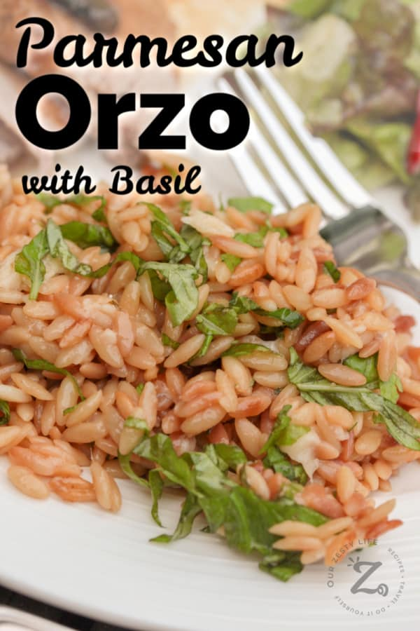 parmesan orzo with basil on a white plate with a fork and salad