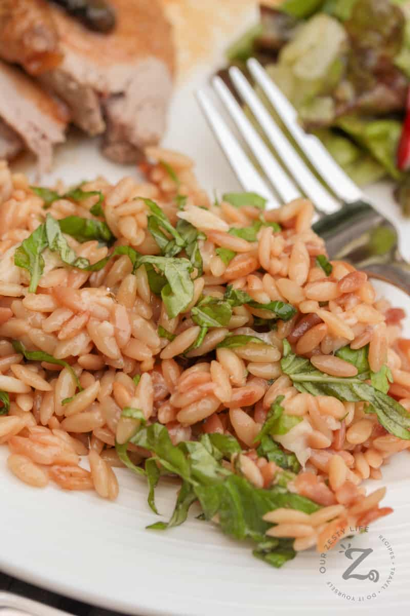 parmesan orzo with basil on a white plate with a fork, salad and pork loin