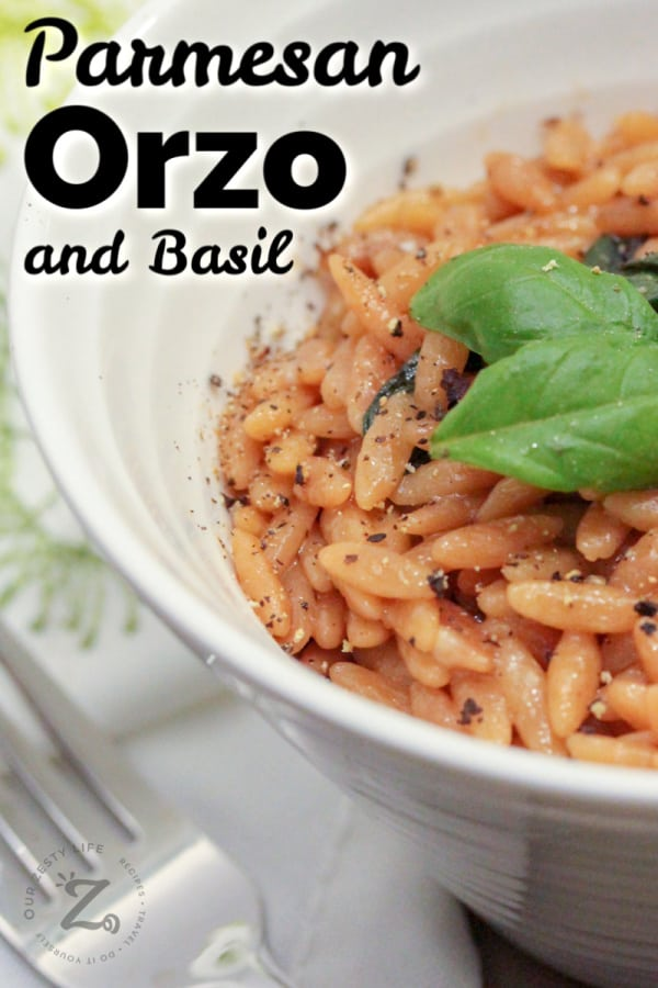 parmesan basil orzo in a white bowl garnished with pepper and basil, with a fork on the side