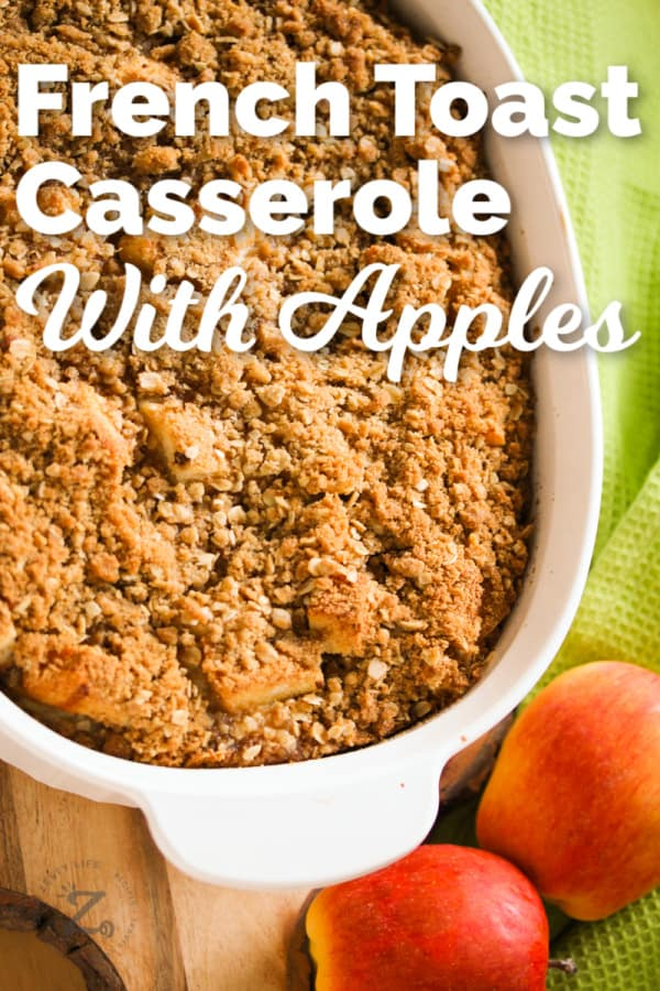 French toast casserole with apples in a white casserole dish with apples an a green towel on the side