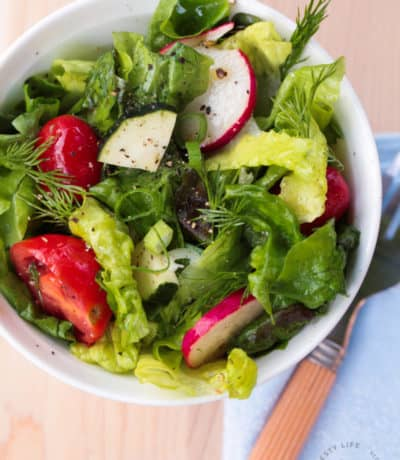 overhead shot of red leaf salad with lemon vinaigrette, with dill, radishes, grape tomatoes and peppers, in a white bowl with a fork and blue napkin on the side