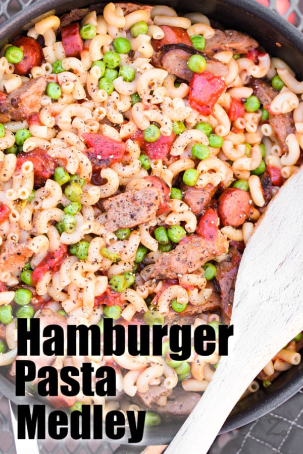 Overhead of hamburger pasta with sausage, peas and diced tomatoes in a skillet with a wooden spoon