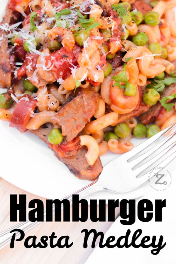hamburger pasta with leftover hamburger patties, sausage, peas on a white plate with a fork