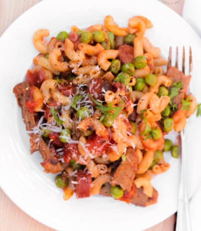 overhead of hamburger and pasta with leftover hamburger patties, sausage, peas on a white plate with a fork