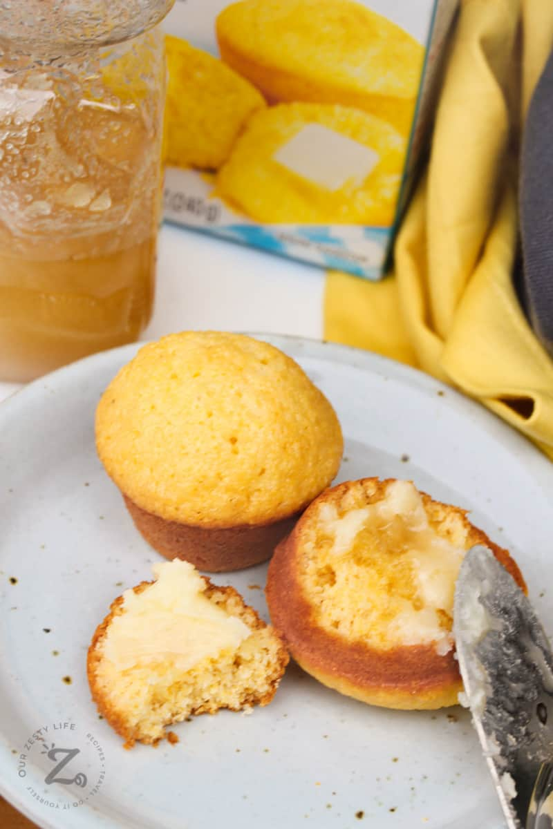honey butter being spread on honey cornbread muffins on a white plate with a honey jar in the background
