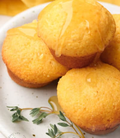four honey cornbread muffins on a white plate, with honey drizzled over the top