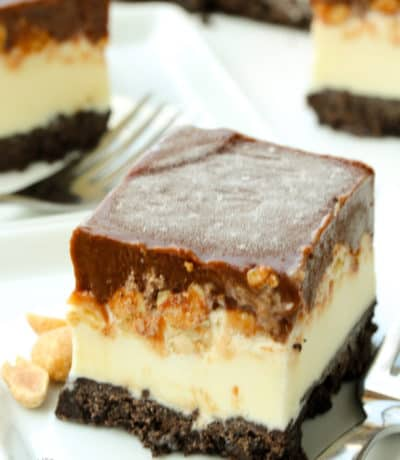 a frosty piece of Buster Bar Ice Cream Cake on a white plate with a fork and a few peanuts on the plate, with a ice cream cake in the background
