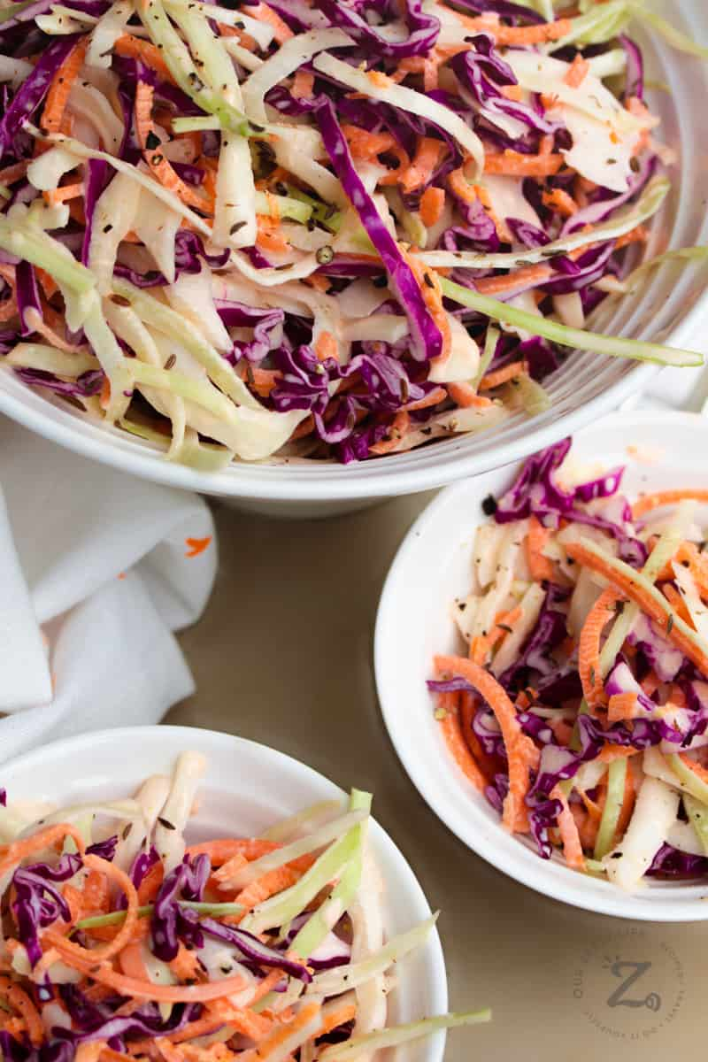 a large white bowl of creamy coleslaw with carrots and cabbage with two servings of coleslaw