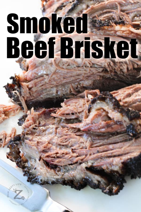 close up of cut pieces of smoked beef brisket on a white cutting board with a serving fork