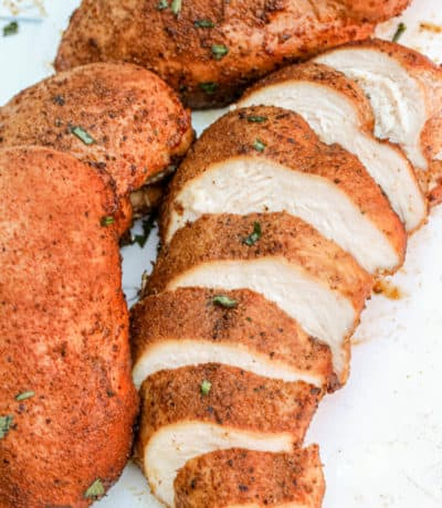 sliced smoked chicken breast with whole chicken breast on a white cutting board