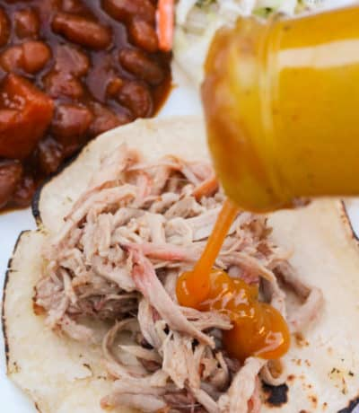 shredded pulled pork shoulder on a grilled corn tortilla,, with added BBQ sauce, baked beans and coleslaw in the background on the plate