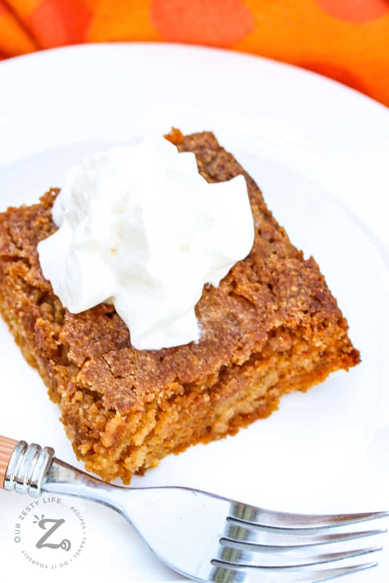 a square of pumpkin pie crunch on a plate with a scoop of ice cream on top with a fork on the plate in the foreground