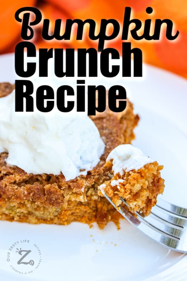 a square of pumpkin pie crunch on a plate with a scoop of ice cream on top with a fork with a bite of pumpkin pie crunch in the foreground