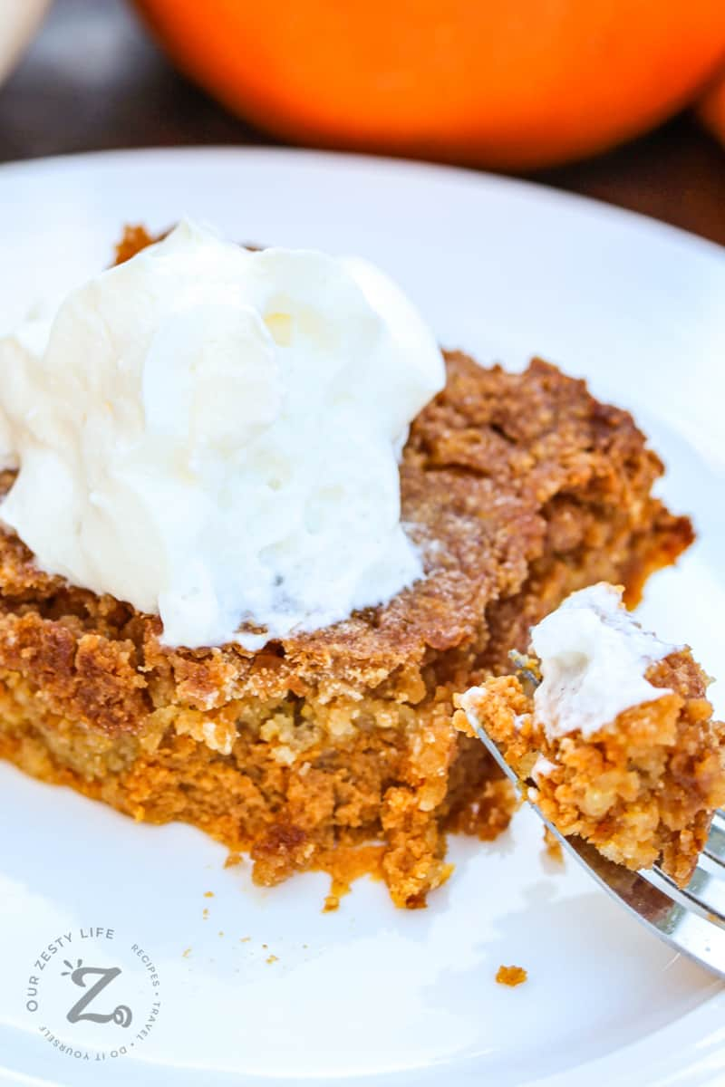a square of pumpkin pie crunch on a plate with whipped cream on top with a fork with a bite of pumpkin pie crunch in the foreground