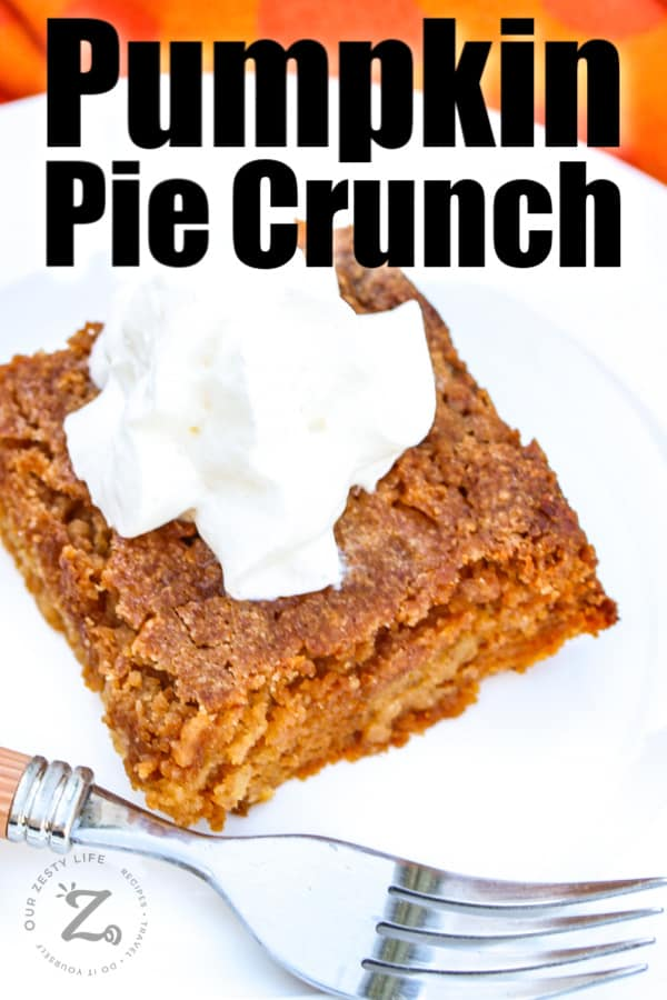 a square of pumpkin pie crunch on a plate with whipped cream on top with a fork on the plate in the foreground