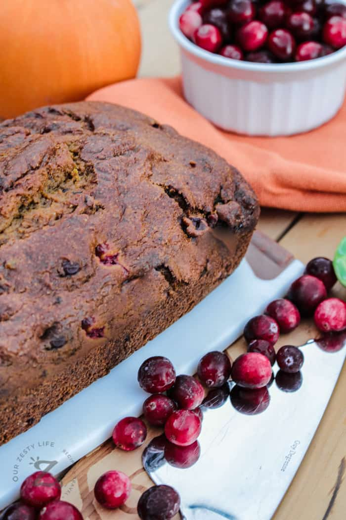 a loaf of cranberry bread on a cutting board and some cranberries on the cutting board  and a bowl of cranberries in the background.
