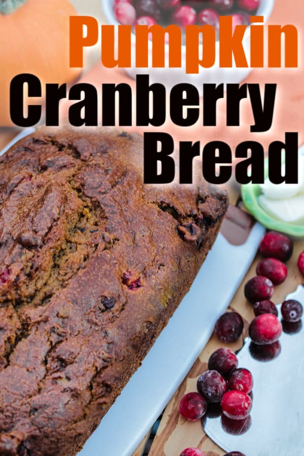 a loaf of pumpkin cranberry bread on a cutting board with a pumpkin and bowl of cranberries in the background