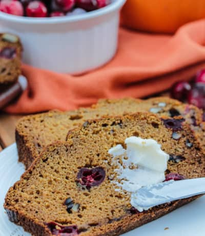 Pumpkin Cranberry Bread slices with butter with cranberries and pumpkin in the background