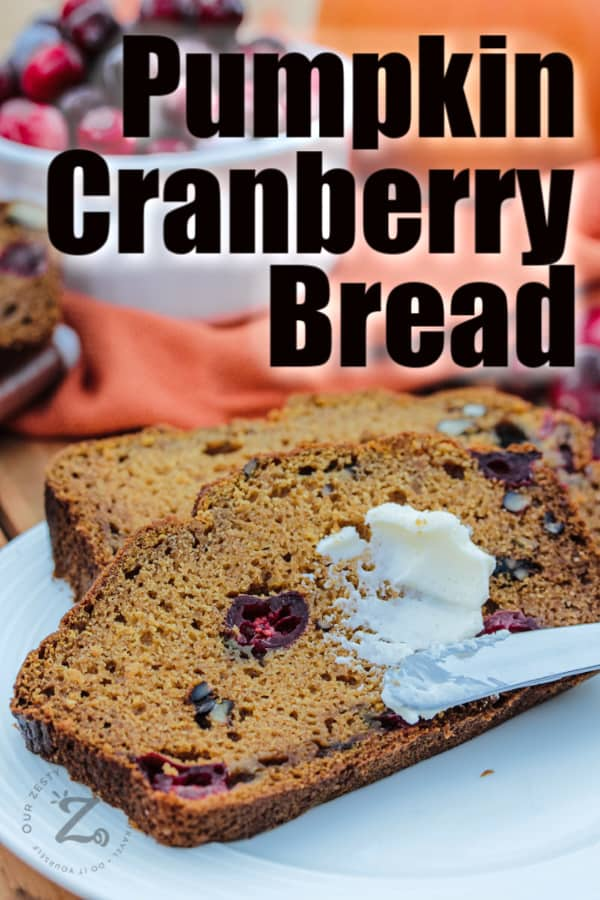 two pieces of pumpkin cranberry bread on a plate with a knife spreading butter on one of the slices. A bowl of cranberries is in the background.