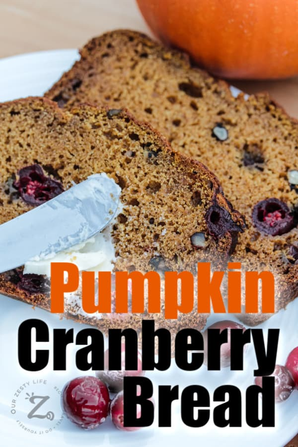 Two slices of pumpkin cranberry bread on a plate with one sliced buttered and some cranberries in the foreground. ans a pumpkin in the background