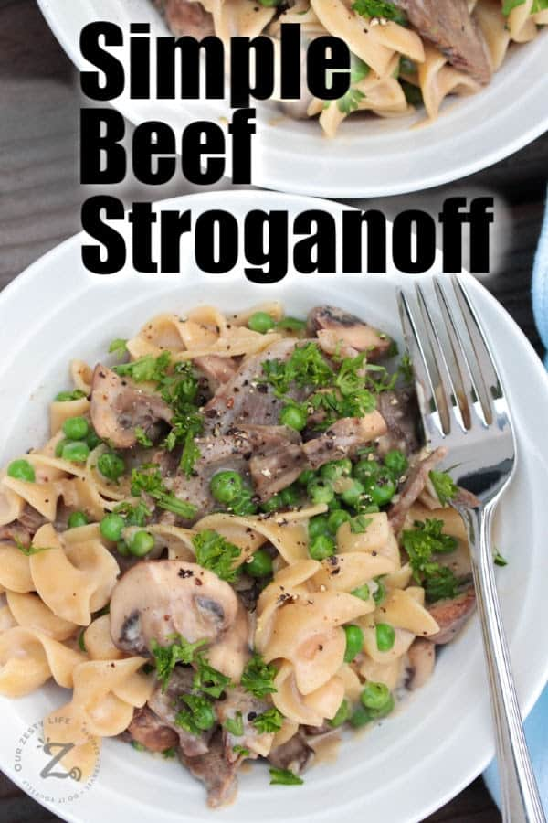 Beef stroganoff with mushrooms and peas on a white plate with a fork