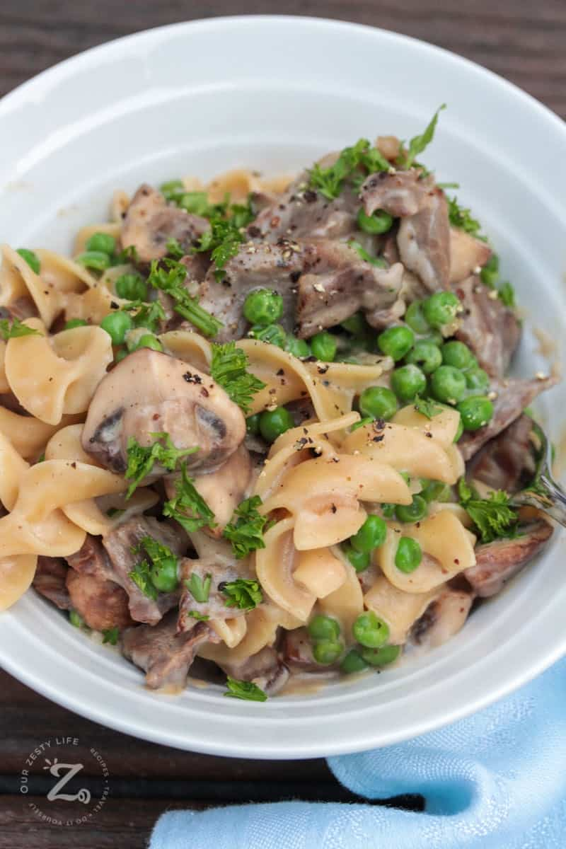 overhead view of beef stroganoff with mushrooms and peas in a white bowl