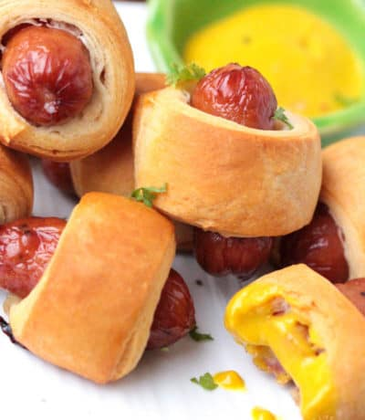 close up of 5 mini pigs in a blanket beside some mustard dipping sauce one has a bite taken from it