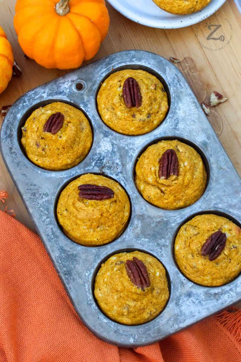 Overheard view of 6 baked pumpkin cornbread muffins in a muffin tin