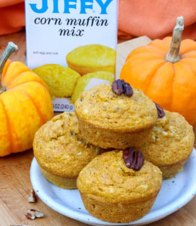 a plate of Pumpkin Cornbread Muffins with nuts on them with Jiffy Corn Muffin Mix and pumpkins in the background
