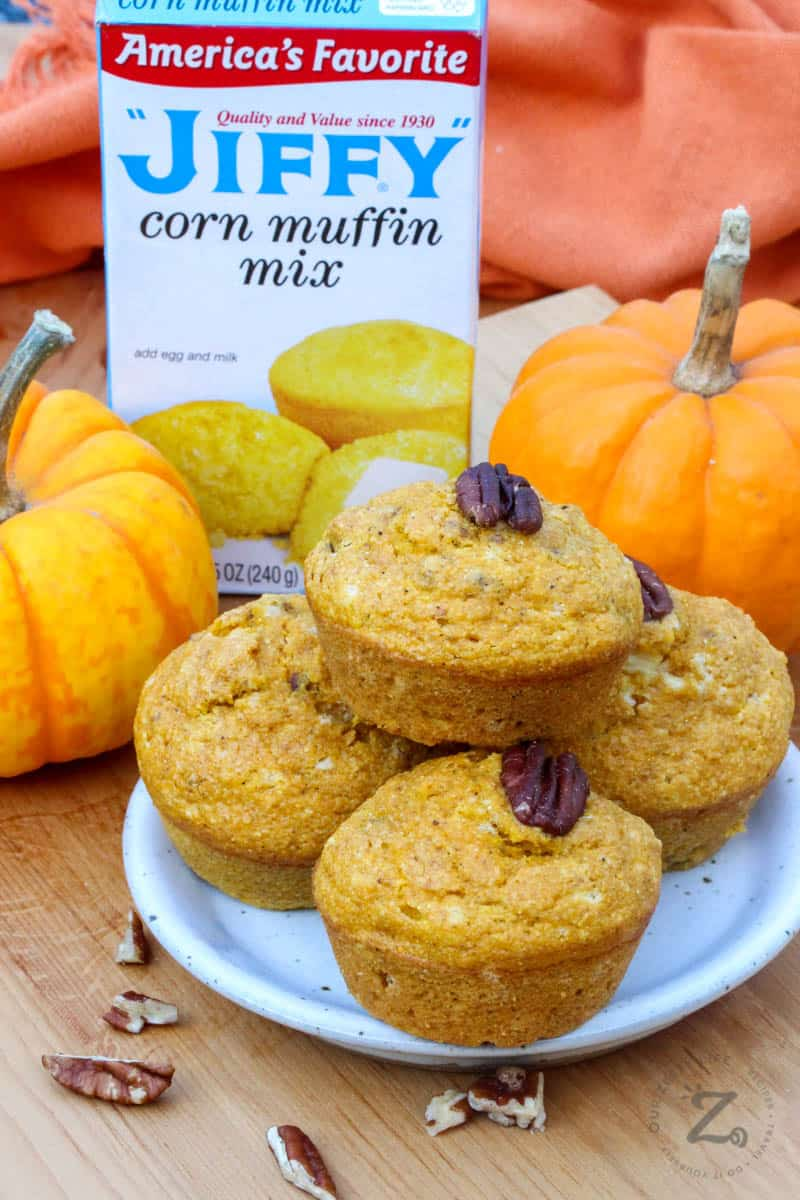 Four  muffins stacked on a plate with a box of Jiffy corn muffin mix in the background and pumpkins