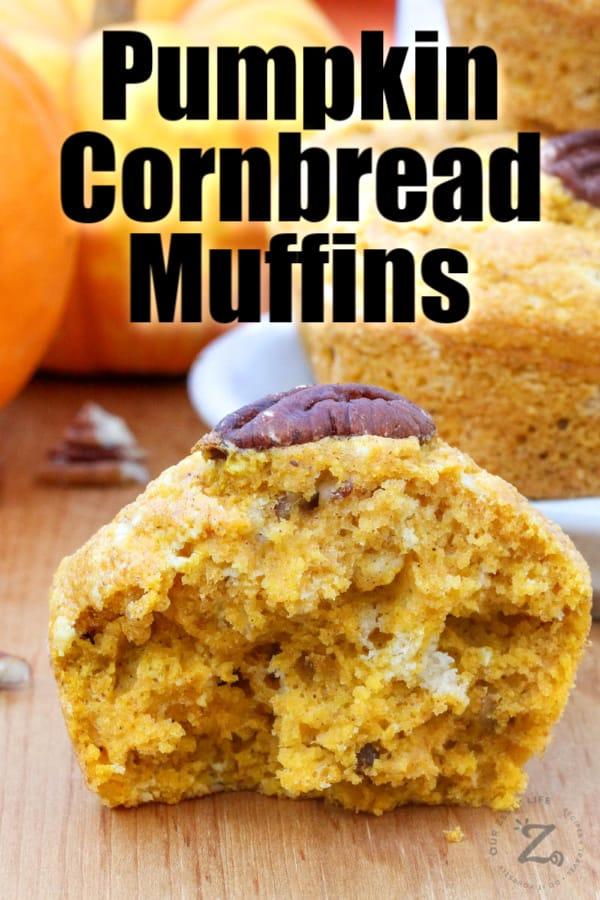 Close up of a pumpkin cornbread muffin cut in half with muffins and pumpkins in the background