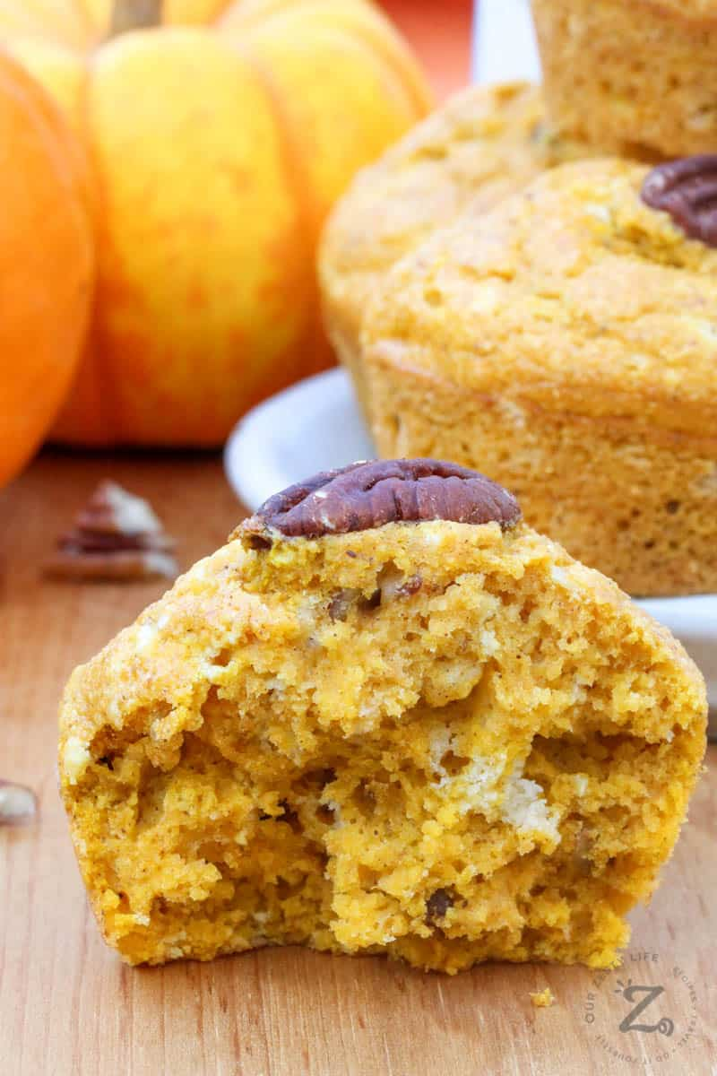 Close up of a pumpkin cornbread muffin cut in half and with some more muffins and pumpkins in the background.