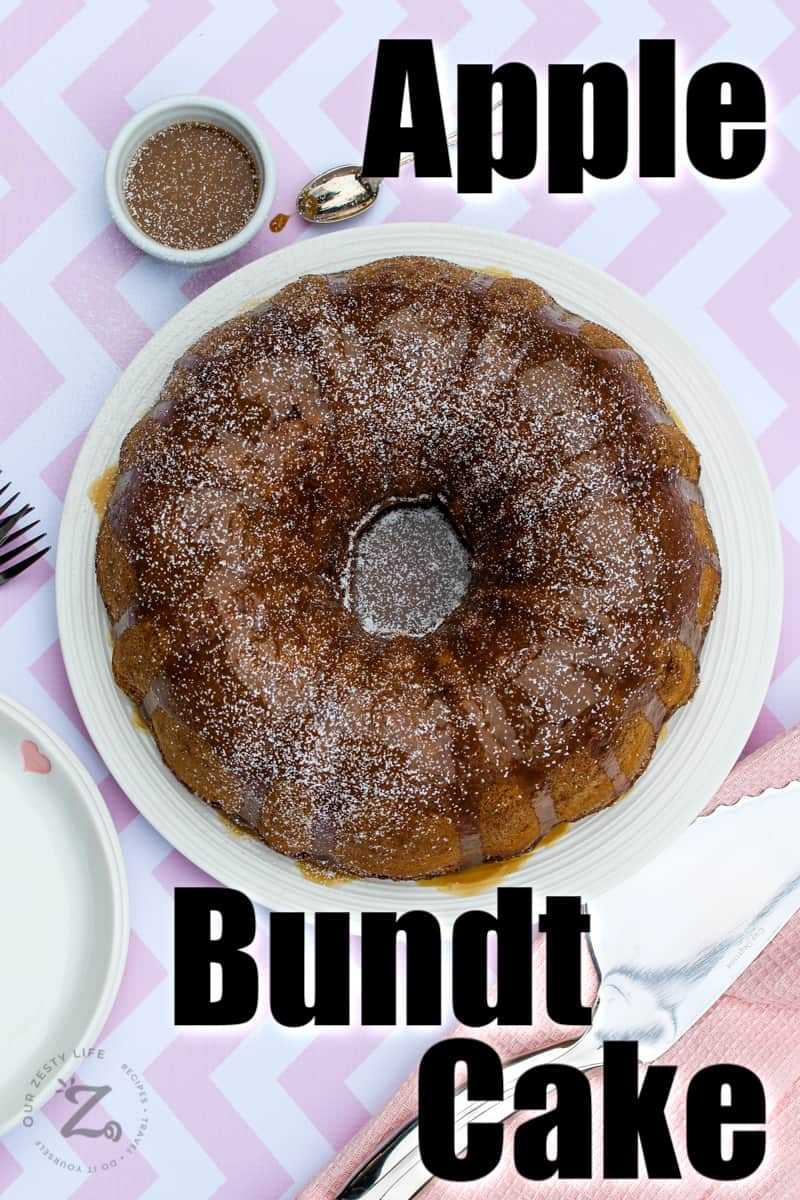 overhead of apple bundt cake with glaze served on a white platter with a small bowl of caramel sauce, a spoon and serving utensil on the side