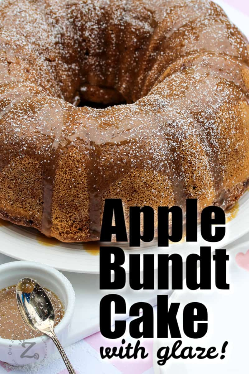 fresh apple bundt cake served on a white platter with a small bowl of caramel glaze and a spoon in foreground