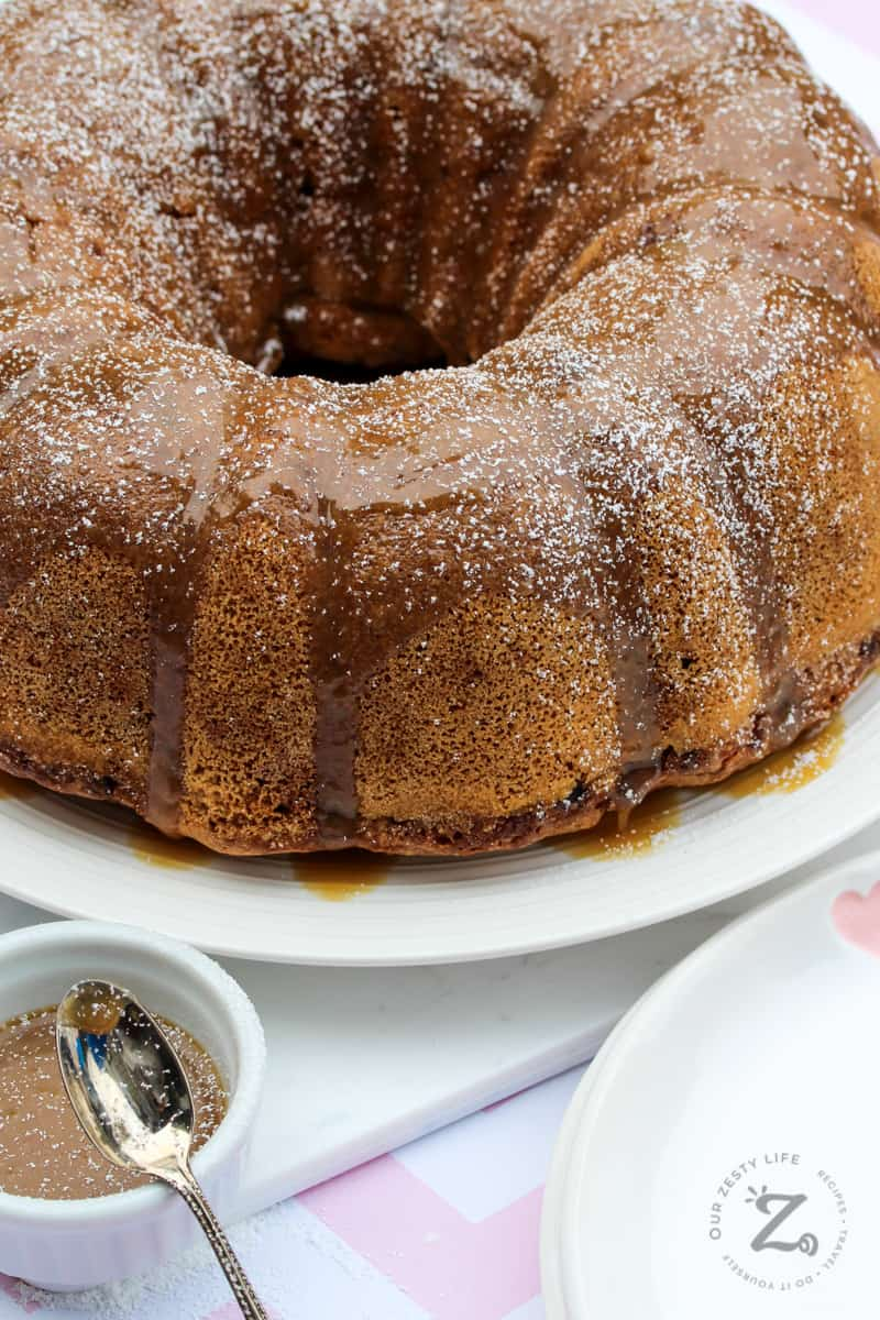 fresh apple bundt cake served on a white platter with a small bowl of caramel sauce and a spoon in the foreground